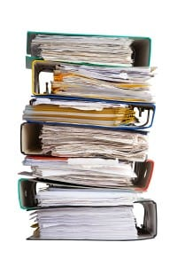 stack of bookkeeping folders with overdue invoices